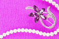 Brooch and pearl necklace on purple background Stock Photo