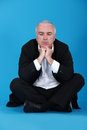 Brooding senior man sat on the floor Royalty Free Stock Image