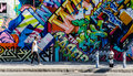 BROOKLYN, NYC, US, October 1 2013: Street art in Brooklyn. Hipster male walking next to a wall of graffiti in Brooklyn, New Royalty Free Stock Photo