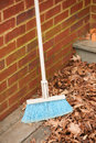 Broom leaning against brick wall to sweep leaves on porch Stock Photo