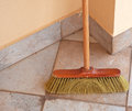 Broom used laying against the wall Stock Photos