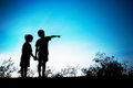 Brother fingers his sister to look to the future.Silhoutte conce Royalty Free Stock Photo
