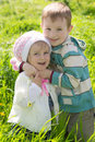 Brother giving hug to sister outdoors in spring Stock Photo