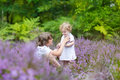 Brother and his baby sister playing together in beautiful purple flowers Royalty Free Stock Images