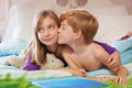Brother kissing sister on cheek blonde haired getting kissed the by red haired lying bed in pajamas Royalty Free Stock Image