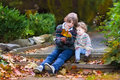 Brother and little sister playing with orange leaves his baby talking Stock Photos