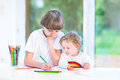 Brother and little toddler sister having fun painting together at a white desk next to a big window with garden view Royalty Free Stock Photos