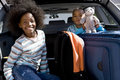 Brother and sister in back of car with luggage boy holding toy smiling portrait Royalty Free Stock Photo