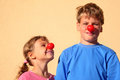 Brother and sister with clown noses stand Stock Images
