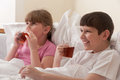 Brother and sister drinking tea in bed. Stock Photo