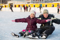 Brother and sister fell while skating and having fun on the ice Stock Images