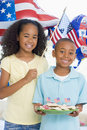 Brother and sister on fourth of July with flags Royalty Free Stock Photo