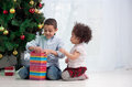 Brother and sister holding Christmas gifts Stock Photos