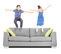 Brother and sister jumping on sofa isolated white background Royalty Free Stock Photos