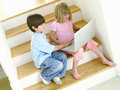 Brother and sister with laptop on stairs elevated view tilt Royalty Free Stock Photo