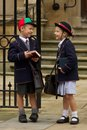 Brother and sister laughing at school gates Royalty Free Stock Photo
