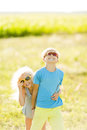 Brother and sister with light curly hair in sunglasses in the field.The boy and the girl are laughing Royalty Free Stock Photo