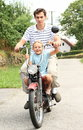 Brother and sister on a motorbike boy in the t shirt sitting the with little girl Stock Photography