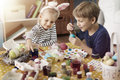 Brother and sister painting easter eggs showing on the egg Royalty Free Stock Image