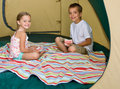 Brother and sister playing cards in tent Royalty Free Stock Images