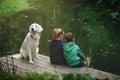 Brother and sister playing girl boy dog outside imitate fishing at a lake Stock Photo