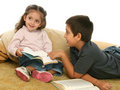 Brother and sister reading books on the floor Stock Photos