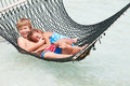 Brother and sister relaxing in beach hammock smiling to camera Royalty Free Stock Image