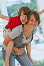 Brother on sister s back making a face teenage girl with elementary aged boy piggy looking at camera with arms outstretched Stock Photos