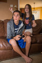Brother and sister sneak attack tween girl about to cover her boys eyes while he is playing a video game both kids are on a couch Royalty Free Stock Photography