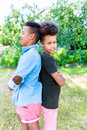 Brother and sister standing in garden two black children shoulder to shoulder Stock Image