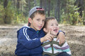 Brother in the woods hugged his little sister and something te a pine forest she says she was surprised laughing Royalty Free Stock Photo