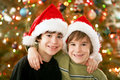 Brothers in christmas hats front of tree Royalty Free Stock Image