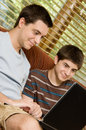 Brothers on the computer two teen looking at a laptop at home Stock Photo