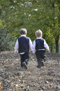 Brothers heading home little boys walking through a plowed garden after harvest Stock Image
