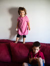 Brothers at home boy playing with toy and girl climbed on sofa Royalty Free Stock Image