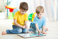 Brothers kids reading book together at home read Stock Images