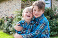 Brothers in matching plaid shirts laughing two young boys with blue hugging and having fun Stock Photo