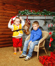 Brothers near christmas tree two decorated pending holiday Stock Images