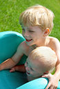 Brothers playing on slide outside close up of two children a baby and his big brother laying at the top of a playground together Stock Photography