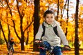 Brothers ride a bike in autumn park close portrait of boy on the bicycle riding with orange leaves Stock Image