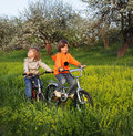 Brothers ride on bikes outdoors Royalty Free Stock Photo