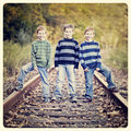 Brothers three standing an old rail tracks with instagram effect filter Royalty Free Stock Image