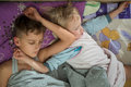 Brothers two boys sleeping together in bed close up Royalty Free Stock Photo