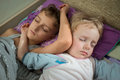 Brothers two boys sleeping together in bed close up Royalty Free Stock Images