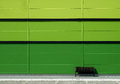 Brown bench in front of green wall Royalty Free Stock Photo