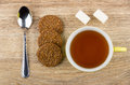 Brown biscuits, teaspoon, lumpy sugar and cup of tea Royalty Free Stock Photo