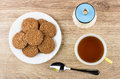 Brown biscuits in white plate, sugar bowl, cup of tea Royalty Free Stock Photo