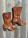 Brown boots leather women on old wooden wall Royalty Free Stock Photography