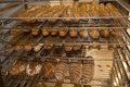 Brown bread loaves on rack. Big scale of production. Baked goods made for wholesale. Royalty Free Stock Photo