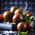 Brown cherry tomatoes with sea salt and green basil on dark tabl Royalty Free Stock Photo